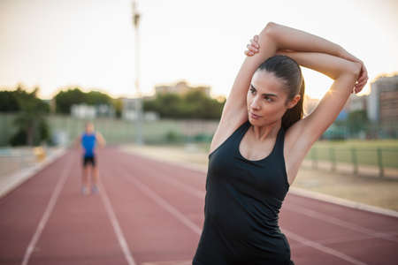 Young woman stretching arm on running track