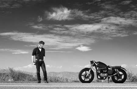 roadside stand: Black and white portrait of mid adult male motorcyclist on highway roadside LANG_EVOIMAGES