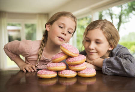 Two sisters gazing at stack of with doughnut holes on kitchen counter LANG_EVOIMAGES