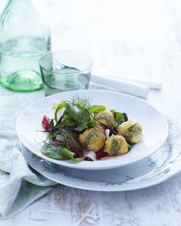 Plate with  fresh sage and bocconcini (small mozzarella balls) fritters with salad