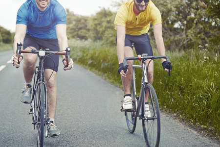 english ethnicity: Cyclists riding on single carriageway, Cotswolds, UK