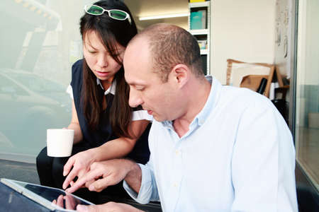 Male and female architects looking at digital tablet in office