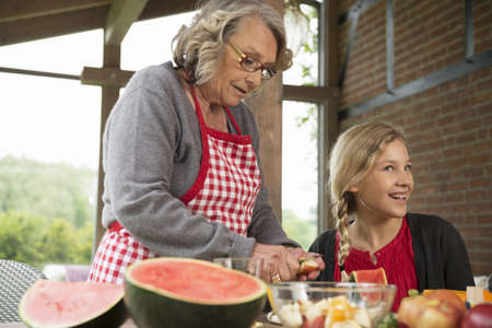 housing lot: Girl and grandmother at kitchen table learning to slice fresh fruit LANG_EVOIMAGES