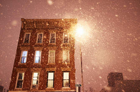 Low angle view of apartment block and street lamp in snow storm