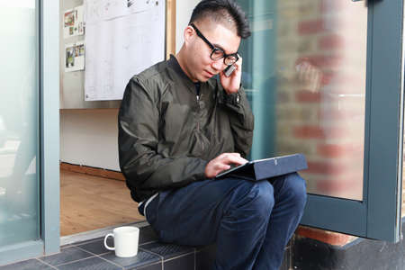 negative area: Male architect using smartphone and digital tablet on office step