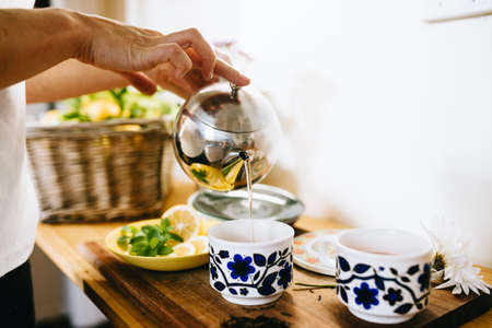 obscuring: Woman preparing lemon and mint tea