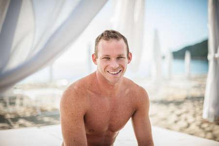 Portrait of young man on beach, Castiadas, Sardinia, Italy LANG_EVOIMAGES