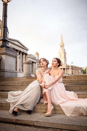 Portrait of two female models posing on steps, Trafalgar Square, London, UK