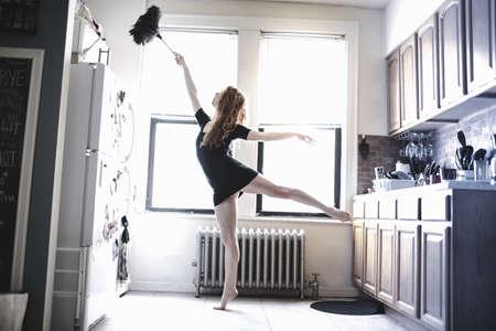 Modern dancer dusting her apartment LANG_EVOIMAGES