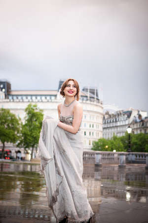 Young woman holding up wet evening gown, Trafalgar Square, London, UK LANG_EVOIMAGES