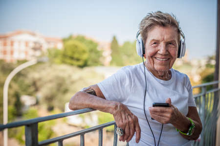 Portrait of a very senior woman leaning on balcony listening to headphones