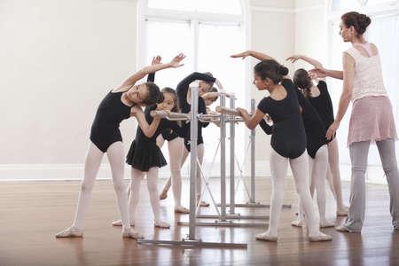 authoritative woman: Ballet teacher teaching group of girls ballet position at the barre