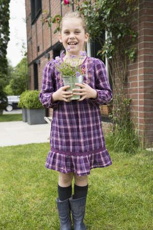 purples: Portrait of girl with flower pot plant in garden