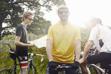 athletic wear: Cyclists stopping on leafy countryside lane, Cotswolds, UK