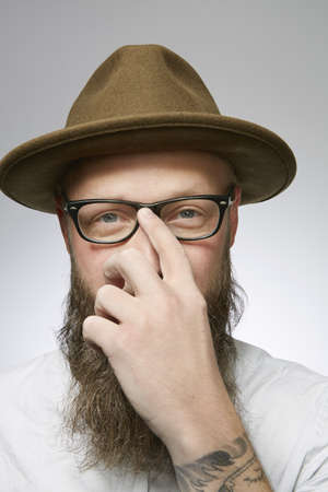 Studio portrait of mid adult man in trilby with hand hiding face