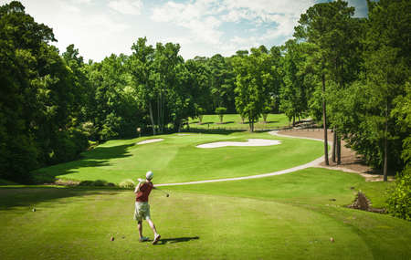 above 18: Elevated view of young male golfer teeing off on golf course, Apex, North Carolina, USA