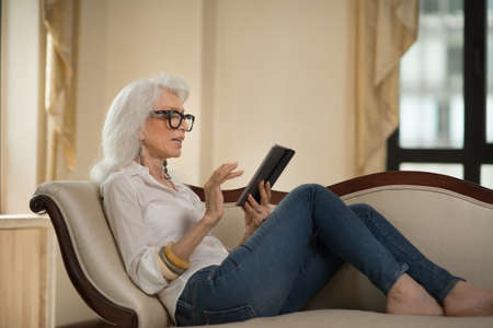 Senior woman reclining on sofa using digital tablet