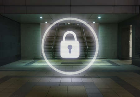 security symbol: Glowing padlock symbol in office building foyer at night LANG_EVOIMAGES