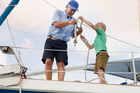 Boy and grandfather knotting rope on sailboat