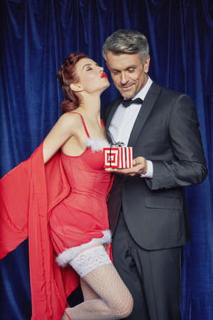 materialism: Burlesque woman giving husband Christmas gift