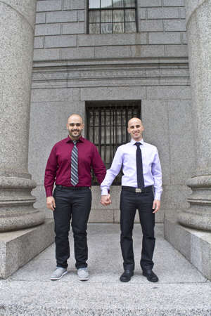 30 years old married couple: Two men holding hands on courthouse steps, just married at City Hall, NYC