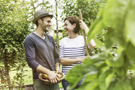 Couple in garden, man holding bowl of apples