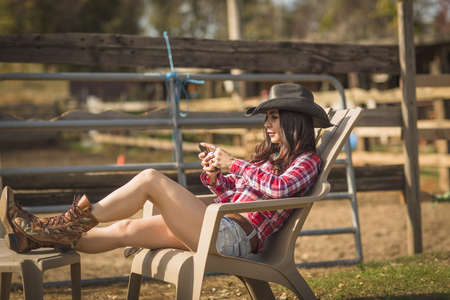 Cowgirl using phone on deckchair on ranch LANG_EVOIMAGES