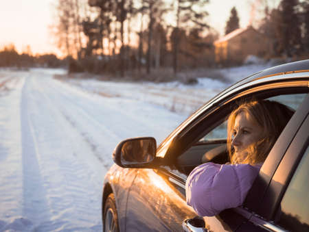 Mid adult woman driving car along snowy road, at sunset