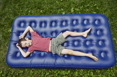 Overhead view of boy lying on inflatable mattress