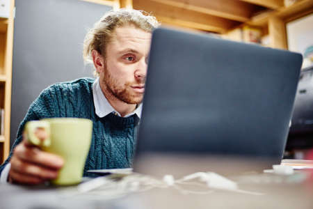 Young man staring at laptop at desk in traditional workshop LANG_EVOIMAGES