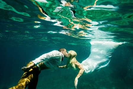 jamaican adult: Couple in wedding attire, kissing, underwater LANG_EVOIMAGES