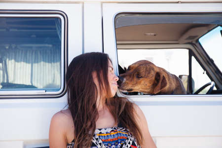 pooches: Pet dog inside camper van, reaching out to lick face of woman beside van