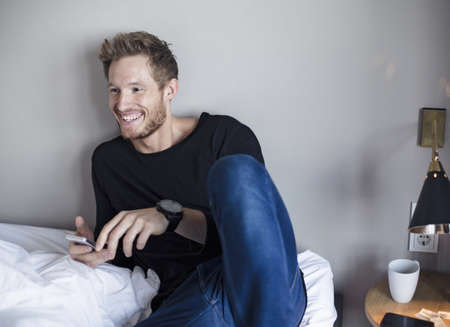 nightstands: Young man relaxing on bed, using mobile phone