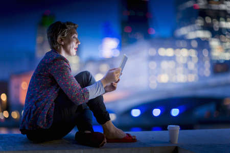 Mature businesswoman sitting on waterfront using  digital tablet at night, London, UK