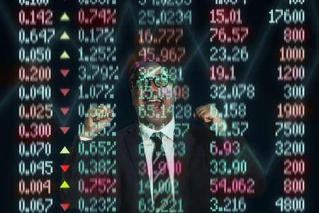 Mature businessman celebrating in front of financial digital display LANG_EVOIMAGES