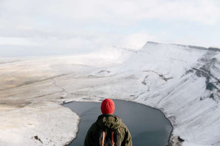 brecon beacons: Rear view of man looking at Llyn y Fan Fach, The Brecon Beacons, Wales, UK LANG_EVOIMAGES