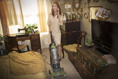 reminisce: Woman vacuuming in vintage dress