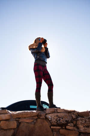 Woman photographing from the edge of Grand Canyon, Arizona, USA
