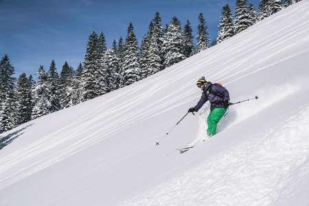 Man skiing down steep slope, Spitzingsee, Germany