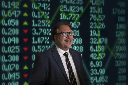 recuperating: Portrait of smiling mature businessman in front of financial digital display