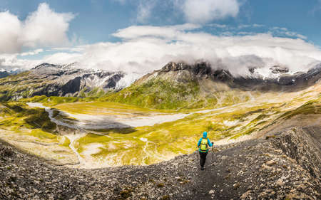 above 18: High angle view of female hiker looking down to valley, Fil de Cassons, Segnesboden, Graubunden, Switzerland