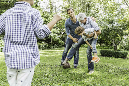 Mid adult man and father playing soccer with sons in garden LANG_EVOIMAGES