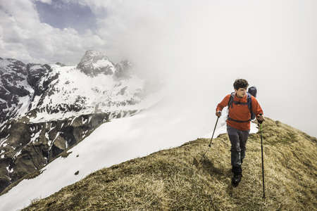 Young man mountain trekking along ridge in Bavarian Alps, Oberstdorf, Bavaria, Germany