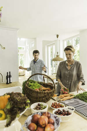 detoxing: Couple preparing fresh vegetables on kitchen counter
