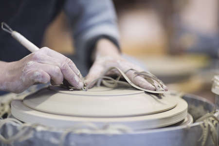 Close up of female potters hands finishing clay plate on pottery wheel