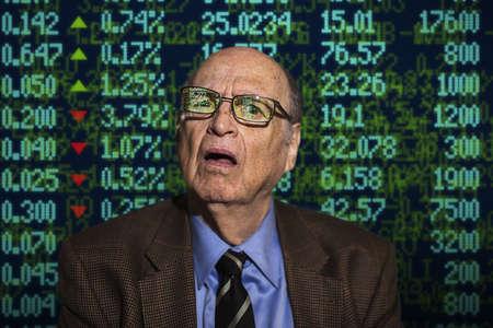 Portrait of confused senior businessman in front of financial digital display