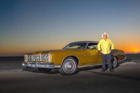 Portrait of senior man standing beside yellow car LANG_EVOIMAGES
