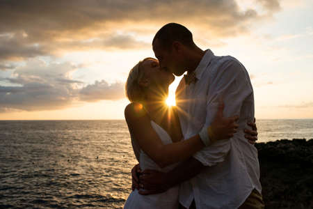 Couple kissing, beside sea, at sunset