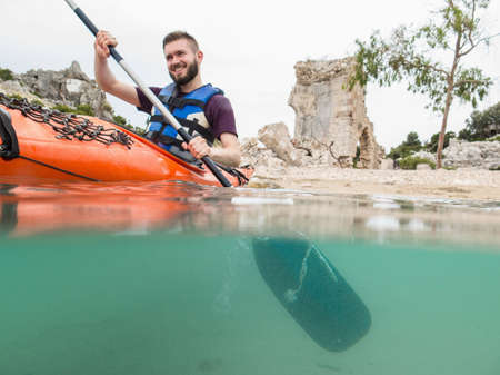 move in: Man kayaking near ancient ruins, Lycian Way, Turkey