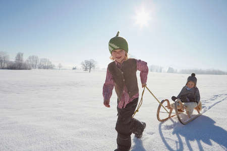 to go sledding: Young boy pulling brother on sled